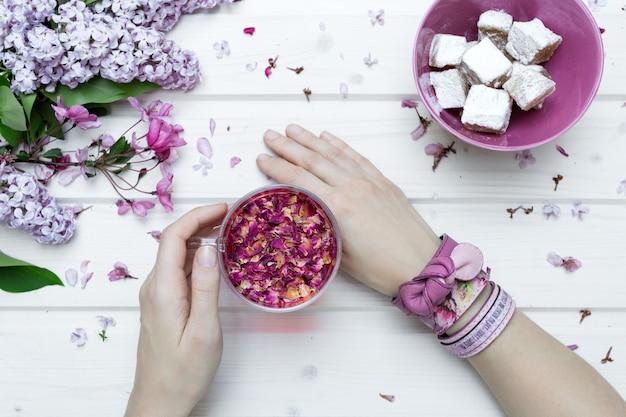 Vue en pov d'une personne avec des bracelets roses tenant une tasse pleine de pétales