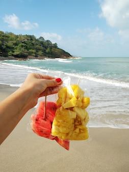 Vue à la première personne d'une fille sur une plage tropicale profitant de la détente et mangeant des fruits