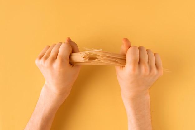 Vue à la première personne des mains masculines brisant un tas de spaghettis isolés