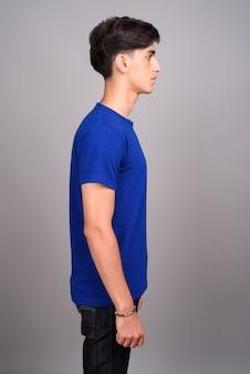 Vue de profil de beau jeune adolescent persan sur fond gris