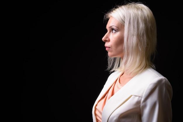 Vue de profil de belle femme d'affaires aux cheveux blonds pensant