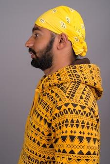 Vue de profil du jeune bel homme indien portant un sweat à capuche