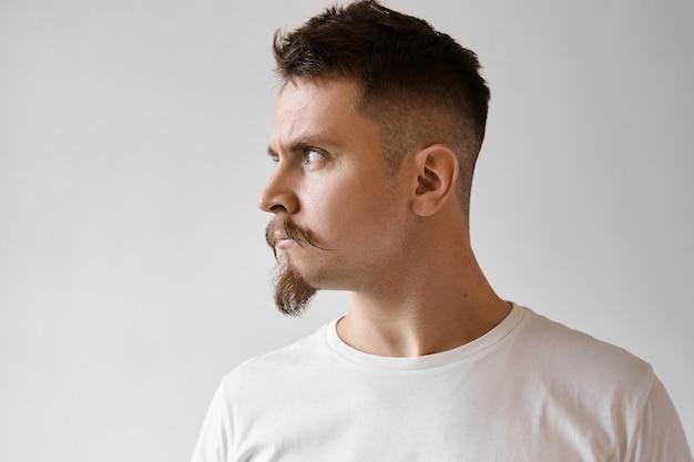Vue de profil du jeune homme de race blanche mécontent féroce avec barbiche, moustache et coupe de cheveux élégante en équilibre isolé en t-shirt blanc à la recherche de suite avec une expression offensée en colère, ne veut pas parler