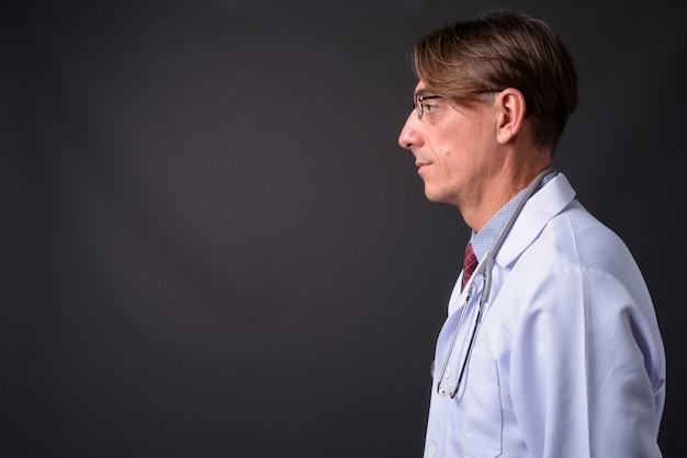Vue de profil du médecin italien beau mature contre mur gris
