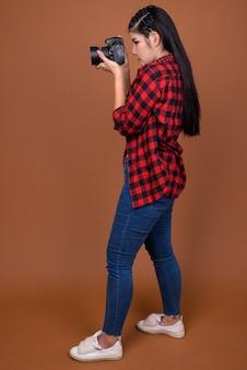 Vue de profil du photographe femme asiatique prenant une photo
