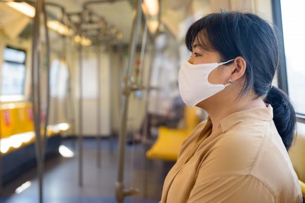 Vue de profil d'une femme asiatique en surpoids avec masque assis à distance à l'intérieur du train