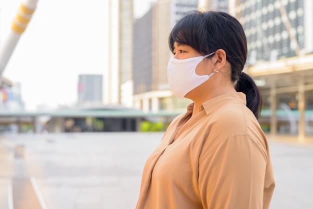 Vue de profil d'une femme asiatique en surpoids avec masque dans la ville