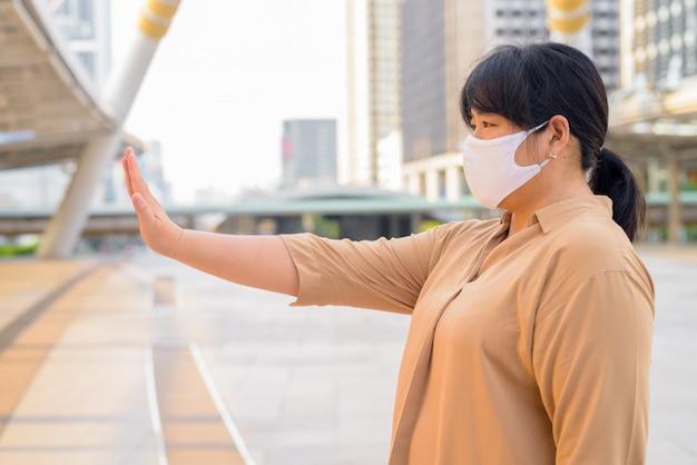 Vue de profil d'une femme asiatique en surpoids avec masque montrant un geste d'arrêt dans la ville
