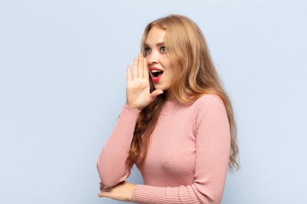 Vue de profil de femme blonde, à la recherche de plaisir et excité, criant et appelant à copier l'espace sur le côté