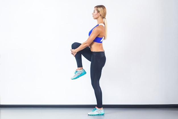 Vue de profil femme sportive blonde, en équilibre sur une jambe. prise de vue en studio