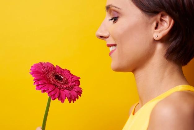 Vue de profil de femme tenant une fleur