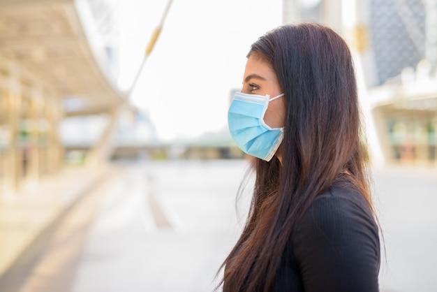 Vue de profil gros plan de la jeune femme indienne avec masque de protection contre l'épidémie de virus corona dans la ville