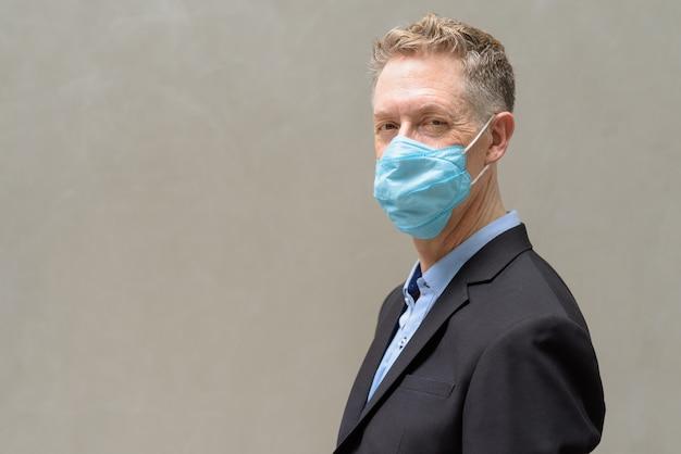 Vue de profil d'homme d'affaires mature avec masque de protection contre l'épidémie de coronavirus à l'extérieur