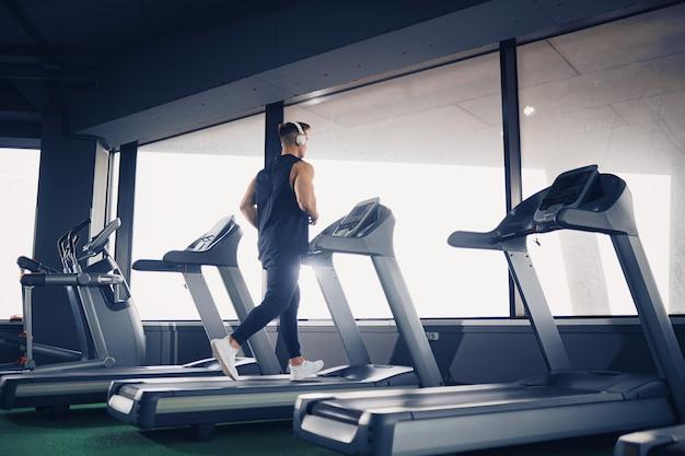 Vue de profil de l'homme fit concentré écouter de la musique dans les écouteurs tout en fonctionnant sur tapis roulant dans une salle de sport moderne avec fenêtres panoramiques, portrait shot
