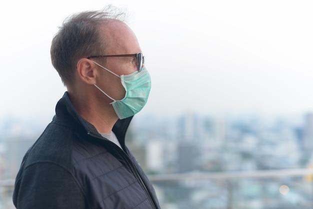 Vue de profil de l'homme mûr avec masque pour la protection contre l'épidémie de virus corona et la pollution dans la ville