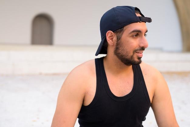 Vue de profil de jeune bel homme indien barbu avec chapeau dans les rues à l'extérieur