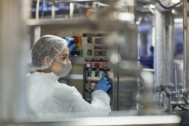 Vue de profil sur une jeune femme appuyant sur les boutons du panneau de commande tout en faisant fonctionner des unités de machine dans une usine alimentaire, espace de copie