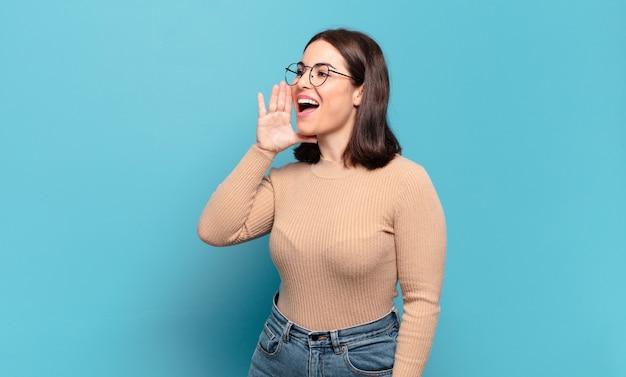 Vue de profil de jeune femme assez décontractée, l'air heureux et excité, criant et appelant à copier l'espace sur le côté