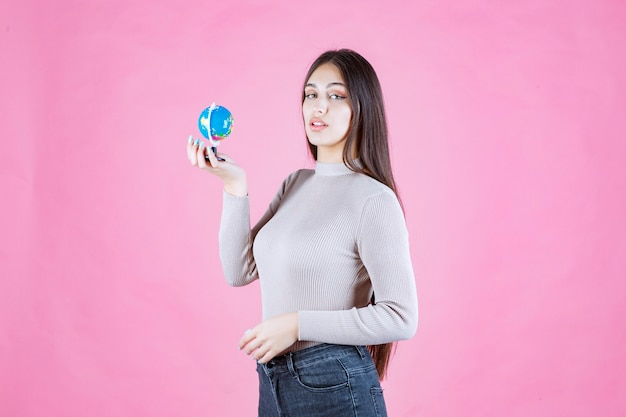 Vue de profil d'une jeune fille tenant un mini globe en toute confiance