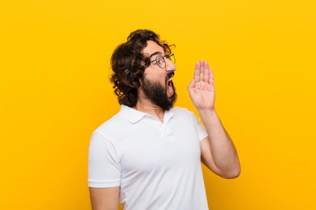 Vue de profil de jeune homme fou, l'air heureux et excité, criant et appelant à copier l'espace sur le côté contre le mur jaune