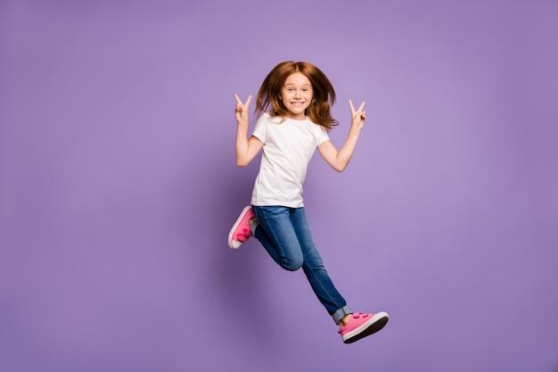 Vue de profil pleine grandeur de funky lady jumping high se réjouissant montrant des symboles v-sign