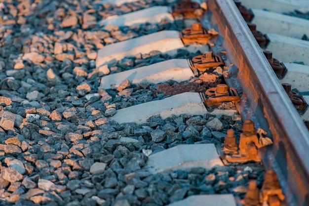 Vue sur les rails, les traverses en béton et le monticule de pierre concassée