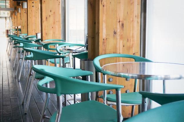 Vue sur une rangée de tables et de chaises vertes dans une cafétéria vide