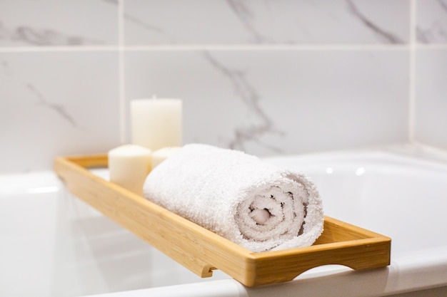 Vue rapprochée des accessoires de salle de bains en marbre blanc, serviettes blanches, bougies et vue latérale de l'espace de copie
