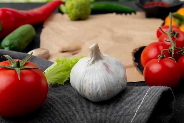 Vue rapprochée de l'ail avec de la tomate et d'autres légumes sur une surface en tissu