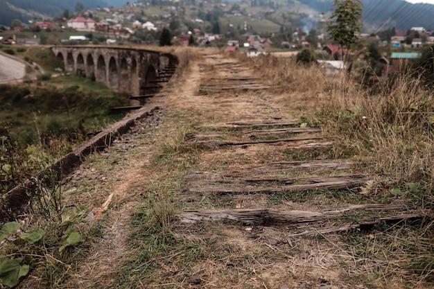 Vue rapprochée des anciennes voies de chemin de fer avec des attaches usées.