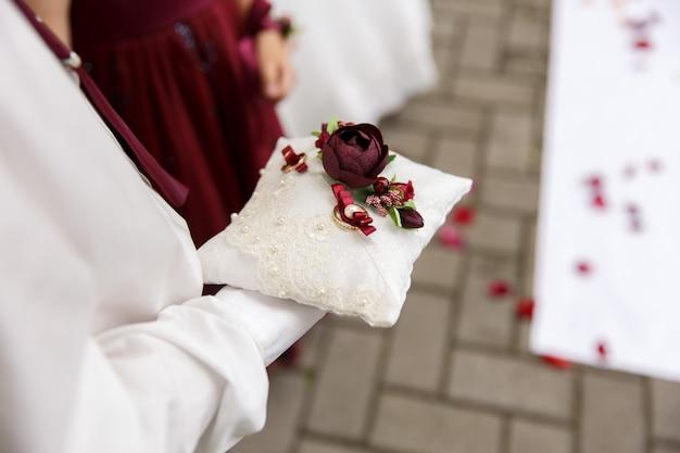 Vue rapprochée des anneaux de mariage sur l'oreiller décoratif