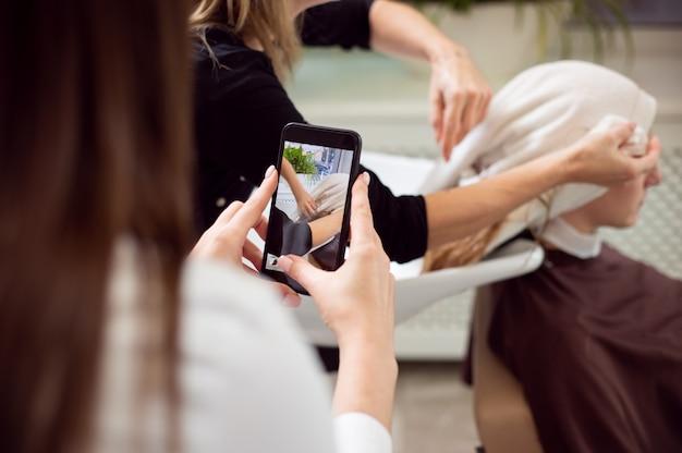 Vue rapprochée de l'arrière d'une femme prenant le tournage d'un coiffeur lors de l'essuyage des cheveux du client