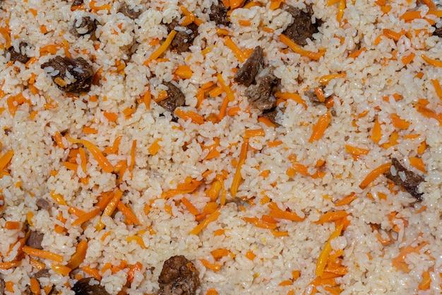 Vue rapprochée de l'arrière-plan de la cuisine savoureuse orientale. plat culinaire asiatique traditionnel - pilaf. ingrédients : riz avec des tranches de viande, graisse et légumes (carotte, ail), épices- recette populaire.