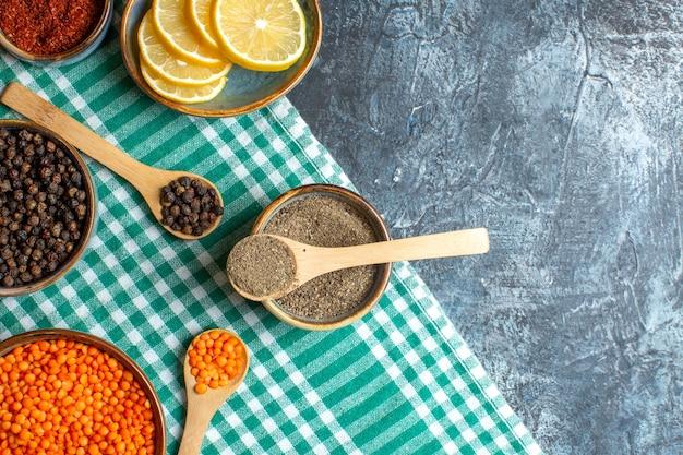 Vue rapprochée de l'arrière-plan du dîner avec différentes épices pois jaune sur une serviette verte sur une table sombre