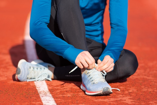 Vue rapprochée, d'un athlète attachant ses lacets de chaussures. homme serrant ses lacets de chaussures assis sur le sol sur une piste de course.