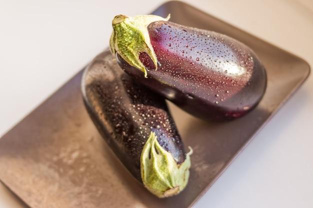 Vue rapprochée d'aubergines humides, fruits d'aubergines avec goutte d'eau isolée