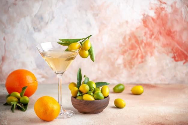 Vue rapprochée avant d'agrumes frais et de vin dans un gobelet en verre sur une surface colorée