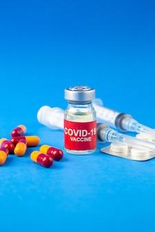 Vue rapprochée avant de l'ampoule de vaccin covid- et capsules comprimés emballés seringues sur fond bleu vague