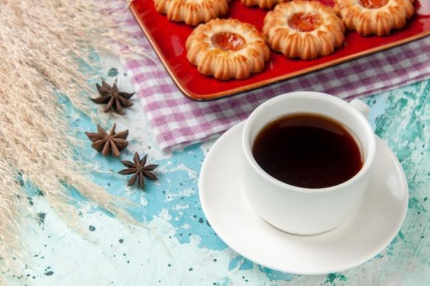 Vue rapprochée avant des biscuits au sucre à l'intérieur de la plaque rouge avec une tasse de thé sur la surface bleue