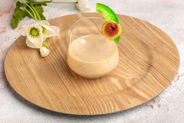 Vue rapprochée avant cocktail crémeux à l'intérieur du petit verre avec des fleurs sur une surface blanche