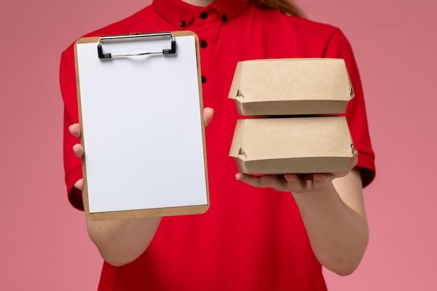 Vue rapprochée avant de courrier féminin en uniforme rouge et cape tenant le bloc-notes et petits paquets de nourriture de livraison sur mur rose clair, service de livraison uniforme
