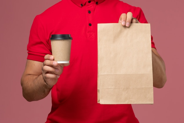 Vue rapprochée avant de courrier masculin en uniforme rouge tenant la tasse de café de livraison et le paquet de nourriture sur le mur rose travailleur de livraison de service travail uniforme masculin