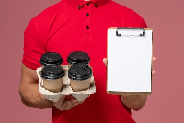 Vue rapprochée avant de courrier masculin en uniforme rouge tenant des tasses de café de livraison avec bloc-notes sur le mur rose