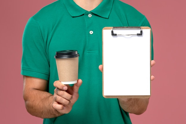Vue rapprochée avant de courrier masculin en uniforme vert tenant la tasse de café de livraison et le bloc-notes sur le bureau rose clair