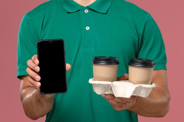 Vue rapprochée avant de courrier masculin en uniforme vert tenant des tasses de café de livraison marron et téléphone sur le travail de bureau rose