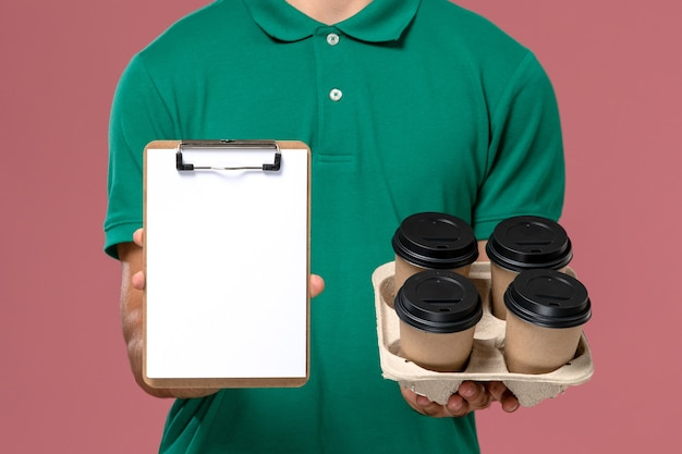 Vue rapprochée avant de courrier masculin en uniforme vert tenant des tasses à café marron et bloc-notes sur bureau rose