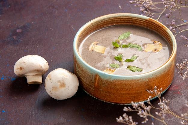 Vue rapprochée avant de la délicieuse soupe aux champignons à l'intérieur de la plaque sur l'espace sombre