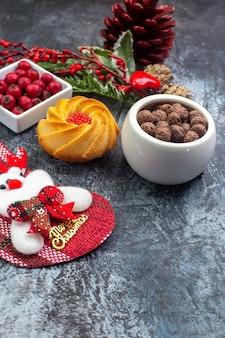 Vue rapprochée avant d'un délicieux accessoire de décoration de biscuits santa claus chaussette et cornell dans un bol de branches de sapin sur une surface sombre