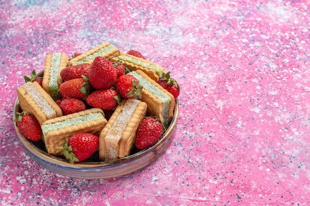 Vue rapprochée avant de délicieux biscuits gaufres avec des fraises rouges fraîches sur mur rose