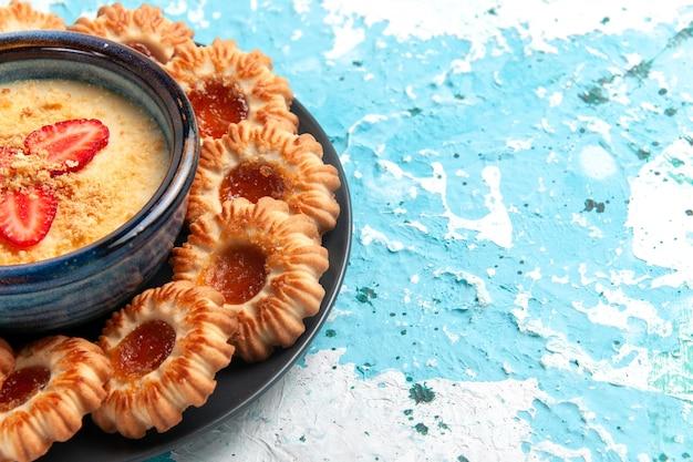 Vue rapprochée avant de délicieux cookies avec confiture et dessert aux fraises sur la surface bleue biscuit sucre biscuit sucré cuire le gâteau au thé